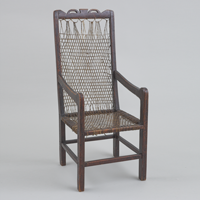A small wooden children's chair with a netted babiche seat. Babiche is an untanned hide, probably caribou in this case, cut into narrow strips.