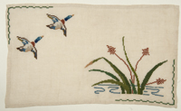 A table linen embroidered in cross-stitch depicting two mallard ducks flying over bulrushes, a common motif for the Crafts Guild of Manitoba.