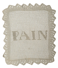 A white crocheted breadbasket liner with the letters P, A, I, N at centre, representing the French word for bread.