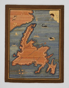 A hooked rug featuring a map of Newfoundland and Labrador marked with ships, a moose, a whale, lighthouses and igloos.