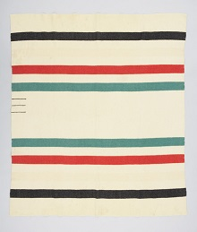 A white rectangular woven wool blanket with a series of horizontal stripes in red, green and black. Three small strips at one edge indicate the size.