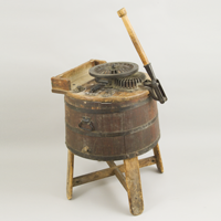 A manual wooden tub washing machine made from the top of a barrel and featuring a large wooden hand crank used during World War II.
