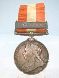 A polished round medal depicting Queen Victoria on a striped red and white ribbon awarded to John Raynor.