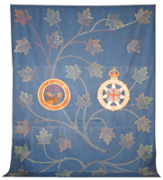 Large blue wall hanging with maple leaf design and a crest for Moose Jaw, Saskatchewan and the Imperial Order Daughters of the Empire crest.