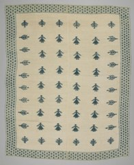 A green and white blanket with simplistic female figures in a grid, bordered on all four sides by pine trees.