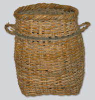 A woven deep rattan basket with two handles, brown and dusty with age but still sturdy. Made of a mix of Chinese rattan and local BC reeds.