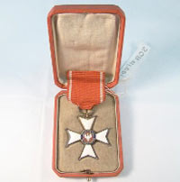 Cross-shaped medal in original box, with a white eagle and the words Polonia Restituta at center, on a red band with white vertical stripes.