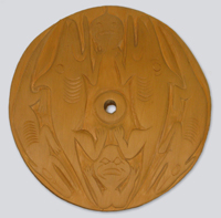 A cedar spindle whorl disk with a carved rendition of the thunder lizard story from the Musqueam people, representing change or regeneration.