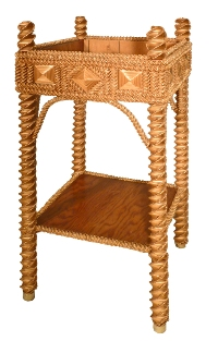 A highly detailed plant stand with tight geometric designs, made from folded oat straw.