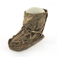 An aged sealskin shoe retaining the basic shape of a human foot and featuring two strips of sealskin as laces.