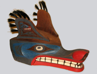 Intricately carved wolf's mask in the coastal British Columbia Salish tradition with vivid red lips, large white teeth and blue highlighted face.