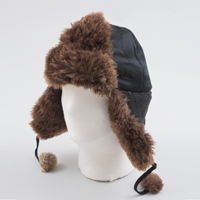 "A black beaver fur lined hat with ear flaps and pom poms hanging from each side owned by legendary northern pilot Wilfrid ""Wop"" May."