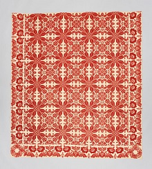 A red and white coverlet with a pattern of repeated poinsettia flowers in a grid, a border of roses, and floral wreaths at the corners.