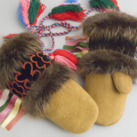 Men's moose hide mittens lined with duffel and trimmed with beaver fur, with distinctive red beaded designs on the wrist and colourful tassels.