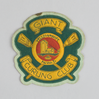 A green, yellow, and red fabric patch with the words 'Giant Curling Club, Yellowknife, N.W.T' embroidered with a tall wooden building.