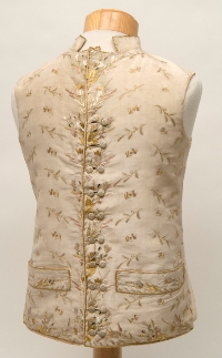 An ornate cream coloured silk waistcoat covered with floral embroidery in a late Jacobean style and buttons covered with decorative stitching.