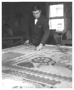 Georges-Édouard Tremblay in a suit inspecting a large hooked tapestry laid out in front of him.