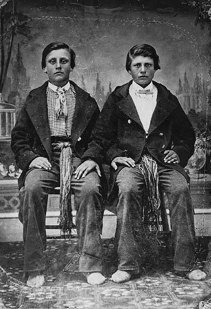 Posed historical portrait of two boys, Charles and Joseph Riel, wearing formal clothes and prominent ceintures fléchées around their waists, 1871.