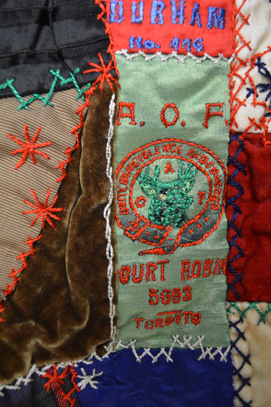 Detail of quilt showing a light green, roughly embroidered Ancient Order of Foresters ribbon.
