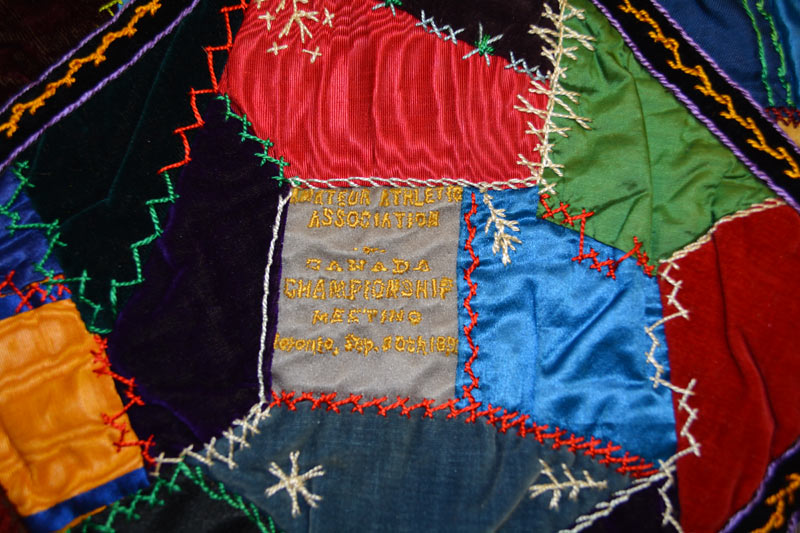 Detail of the quilt reading 'Amateur Athletic Association of Canada Championship Meeting' in yellow.