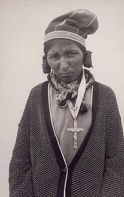 Portrait photograph of an Innu woman wearing a bonnet with a tight curl of hair beside both ears, circa 1930.