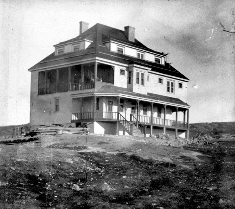 A three-storey, white residential style building perched on rocky coastal terrain, circa 1920.