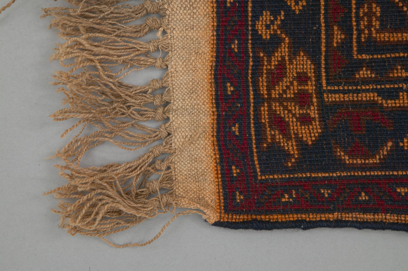 A detailed view of an Afghani rug showing the knotted wool fringes surrounding the edges and the skillful tight weave of the rug itself.