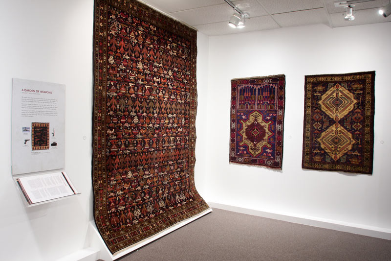 Various Afghani rugs depicting war scenes on display at the Textile Museum of Canada.