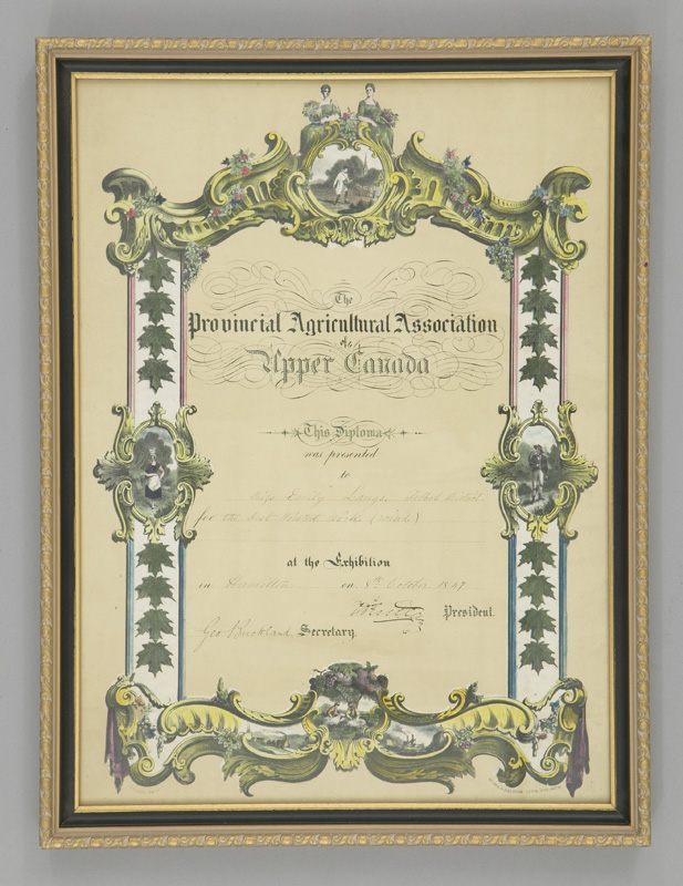 Framed certificate with ornate gold border issued in 1847 for best worsted work, awarded to Emily Lang in Hamilton, Ontario.