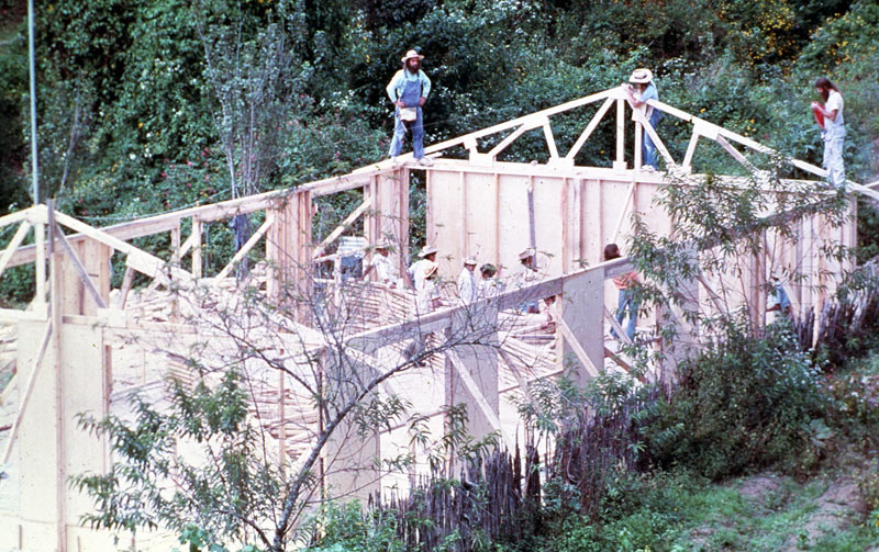 Several men stand on the partially completed lumber frame of a school under construction near Itzapa in the 1970s.