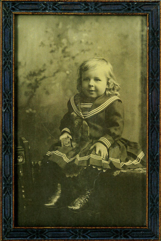 Original framed posed portrait of a young boy, Charles Sharpe, with long curly hair and large leather boots, wearing the sailor suit, circa 1900.