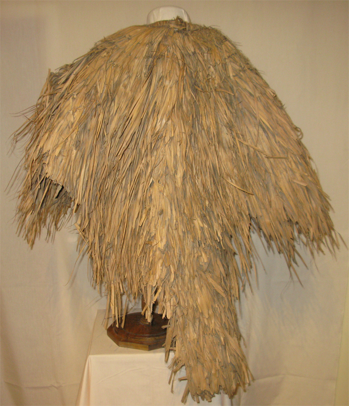Rear view of a traditional Chinese rain cape, showing the many layers of reeds bundled from the shoulders that make it rain resistant.