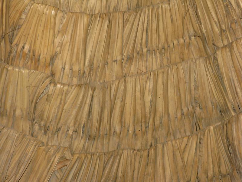 Close up view of a traditional Chinese rain cape, showing the many layers of reeds bundled from the shoulders that make it rain resistant.