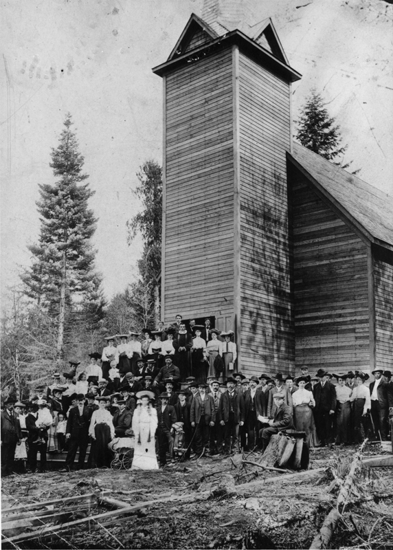 Large congregation of Trinity Norwegian Lutheran Church gathered in front of the original tall wooden church.