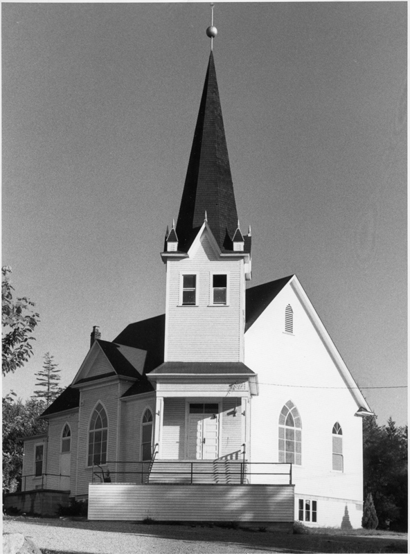 The small white Trinity Norwegian Lutheran Church with tall pointed steeple located in Annieville, British Columbia.