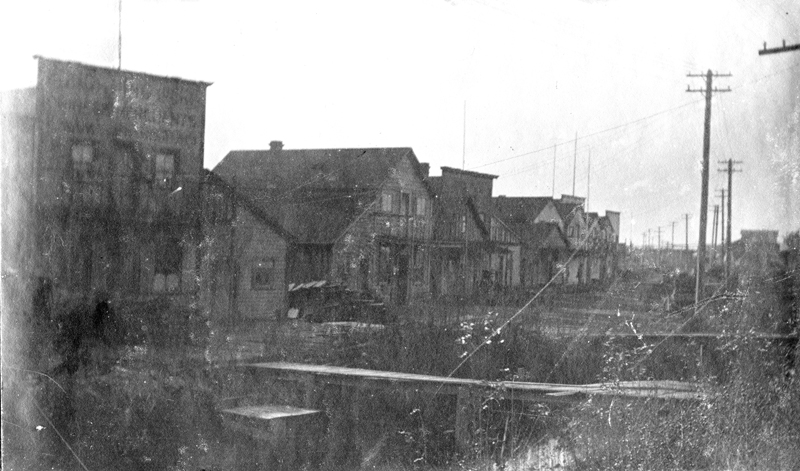 An early 20th century photograph of Ladner, British Columbia. Wooden shops line a mud road, lost to fire in 1929.