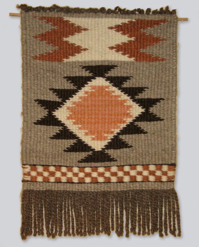 A woven wool rectangular wall hanging with orange and white triangular designs, created by Barb Cayou of the Musqueam Nation.