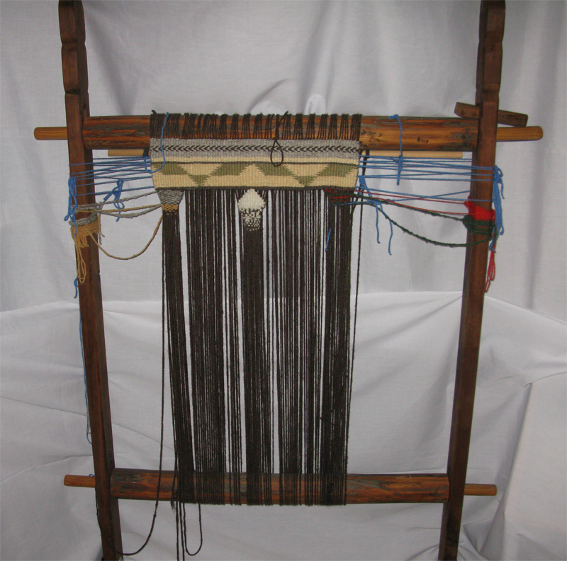 An example of a traditional Salish loom, four sturdy sticks form a square as the warp is stretched across the center.