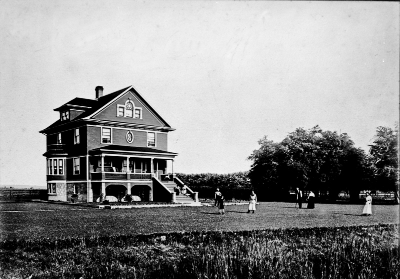 The large three-story Kirkland House stands with a small party playing croquet in the well trimmed yard.