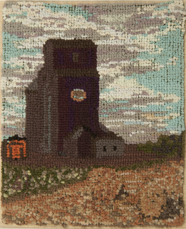 A rug hooked mat depicting a tall brown prairie grain elevator against a blue sky with a lush field in the foreground