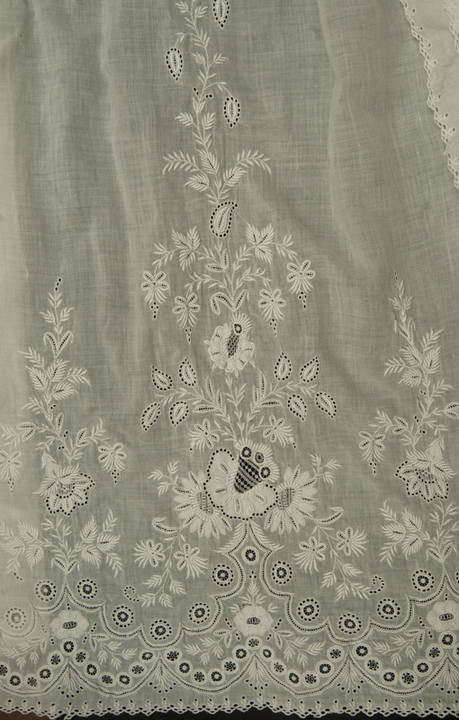 Detail view showing the intricate Ayrshire style floral embroidery decorating the hem, white 19th century christening gown