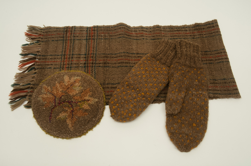 Coarse brown bison wool scarf, mittens and hat. Scarf decorated with a tartan pattern and hat with a branch of yellow maple leaves.