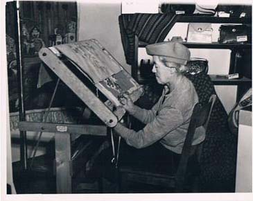 An elderly Marilyn MacTaggart hooking a rug at her angled work table in Manitoba, 1949.
