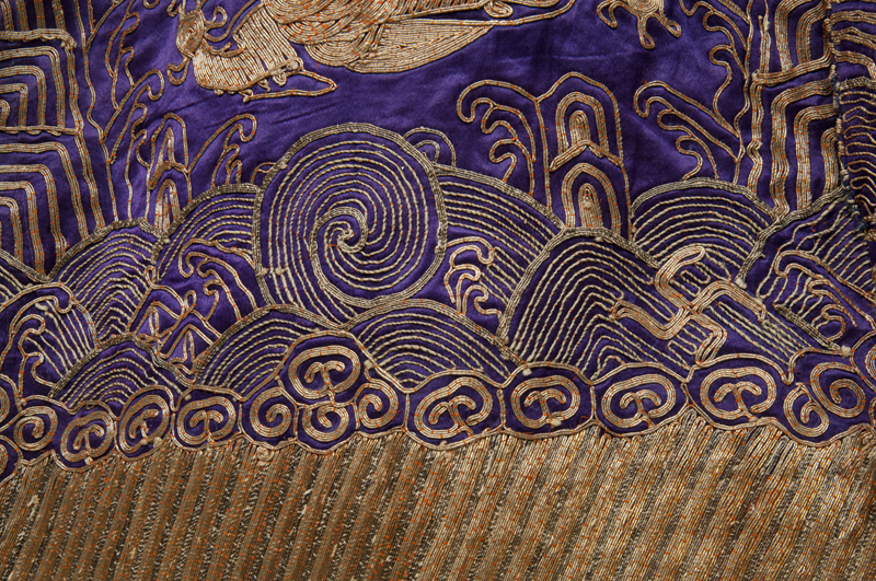 Detail showing ornate waves and swastikas signifying good luck in couched gold thread on a purple silk background.