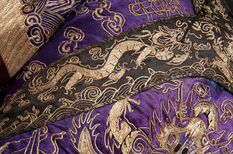 Detail showing dragons running along the robe's collar and sleeves in couched gold thread on a dark silk background.