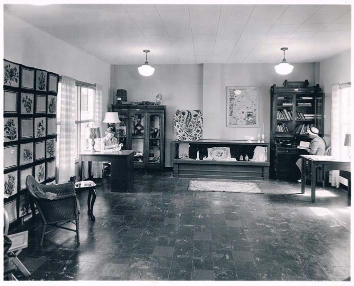 Historical photo of a sparse Guild gift shop. Some ornate projects hang from the wall like tapestrys, including the wildflower.