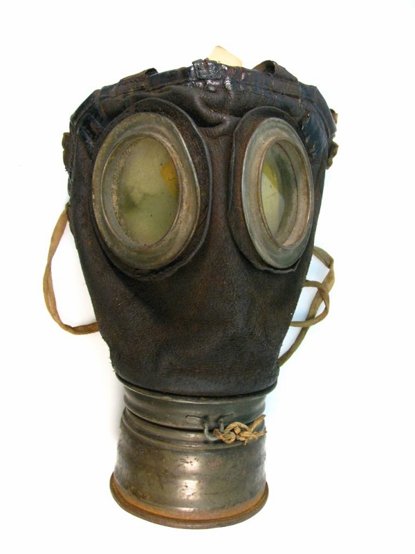 A German gas mask from 1917 with a brown leather face piece, steel rimmed glass lenses, and a steel breathing apparatus.