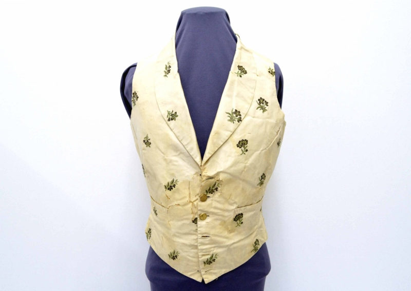 A hand-sewn vest made of cream-coloured corded silk and decorated with embroidered green flowers, owned by Josiah Burr Plumb.