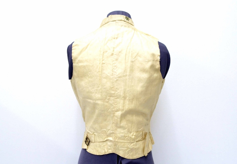 Rear view of a vest made of cream-coloured corded silk with small belt with a metal clasp, owned by Josiah Burr Plumb.