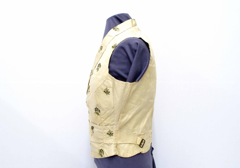 Side view of a hand-sewn vest made of cream-coloured corded silk and decorated with embroidered green flowers, owned by Josiah Burr Plumb.